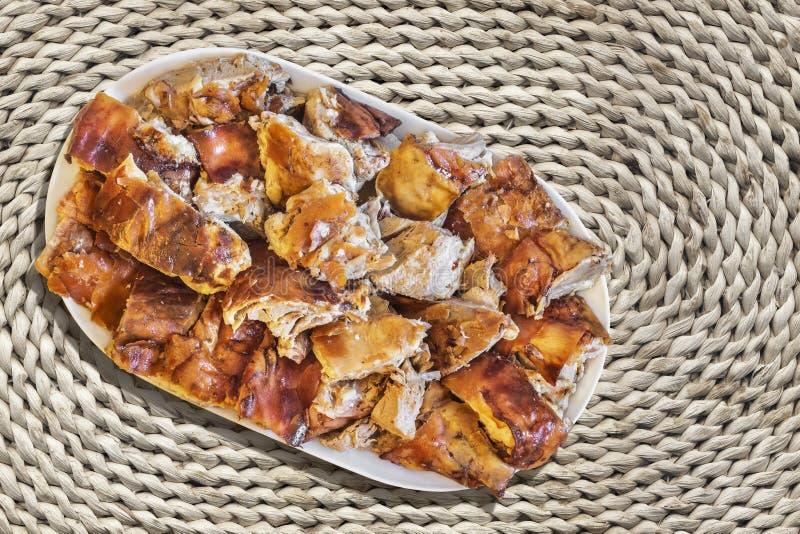 Tellervoll Spucken gebratene Schweinefleisch-Scheiben eingestellt auf rauer rustikaler Raffiabast gesponnene Platz-Matte stockfotografie