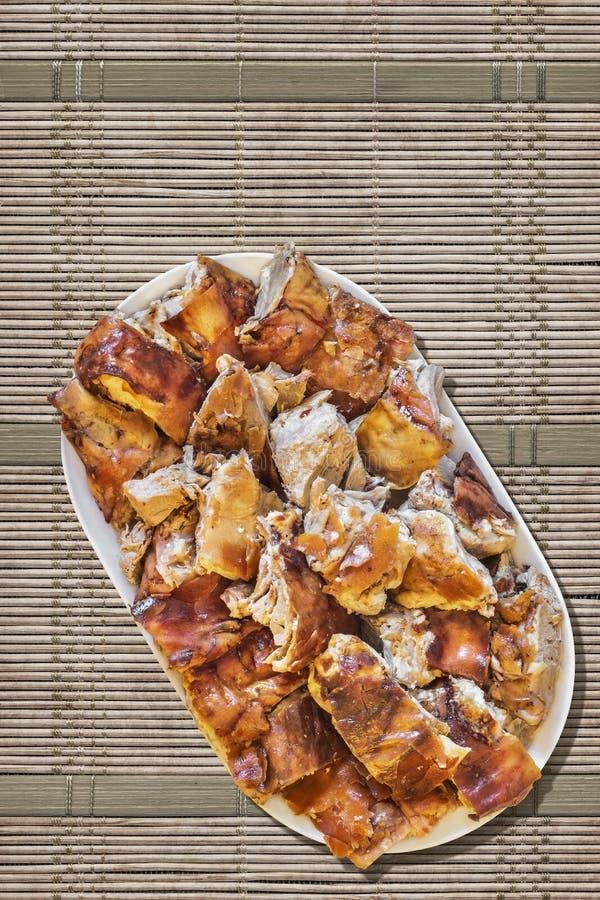Tellervoll Spucken gebratene Schweinefleisch-Scheiben eingestellt auf Straw Place Mat Grunge Surface lizenzfreies stockbild