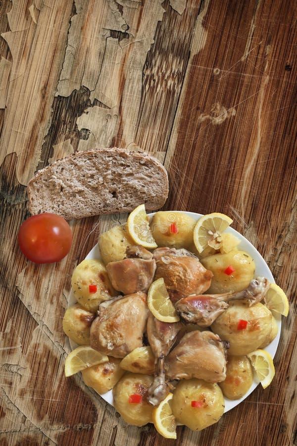 Tellervoll von Fried Chicken Legs und von Kartoffel auf altem Holz stockfotografie