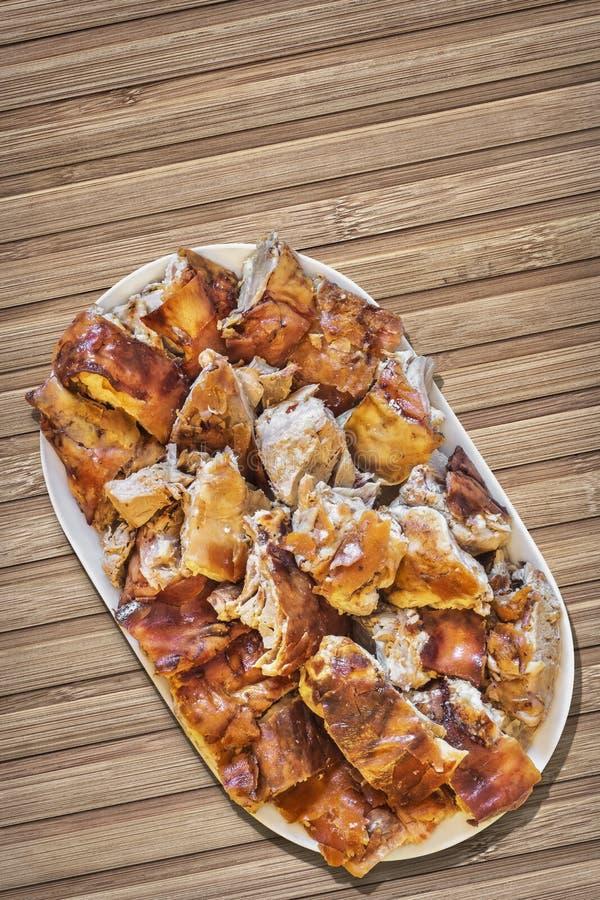 Tellervoll von frisch spucken die gebratenen Schweinefleisch-Scheiben, die auf Weinlese-rustikale Lattenbambusplatz-Matte eingest stockbild