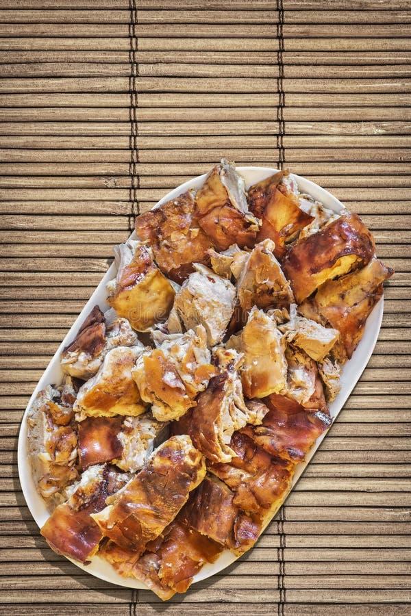 Tellervoll von frisch spucken die gebratenen Schweinefleisch-Scheiben, die auf Weinlese-rustikale Lattenbambusplatz-Matte eingest stockbilder