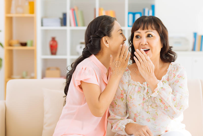 Telling a secret. Mature women telling a secret to her surprised friend royalty free stock photography