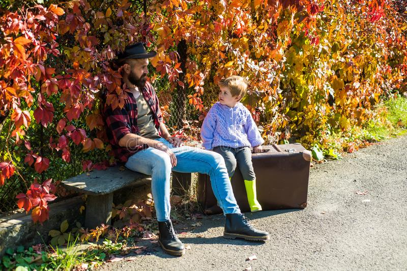 Telling stories about past times. Father with suitcase and his son. Bearded dad telling son about travelling. Traveler royalty free stock photo