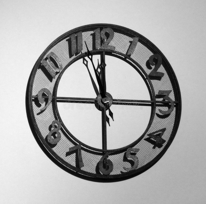 Telling Time. Old fashioned analog metal clock hanging on a wall, approaching the noon (or midnight) hour stock images