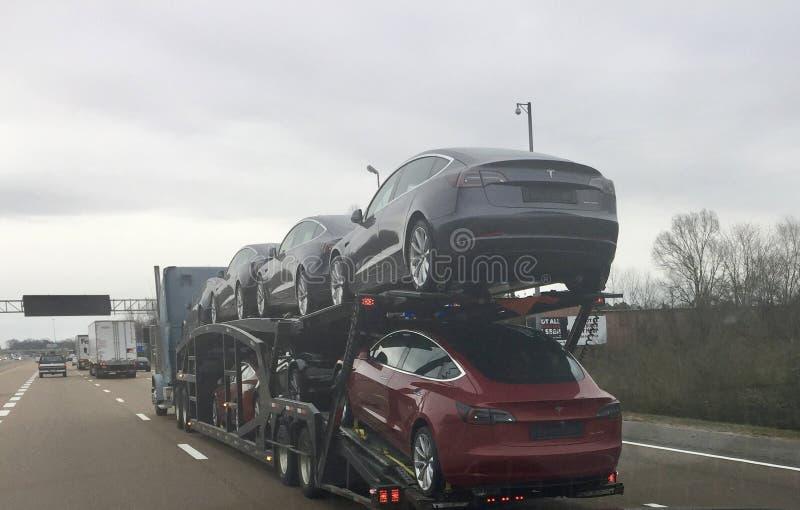 Telsa Model 3 die Auto's aan de Autopartij worden geleid stock foto
