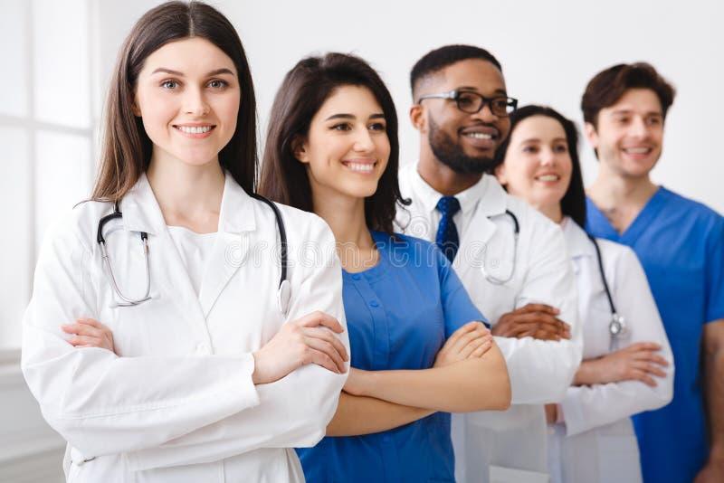 Tem av säkra doktorer och allmäntjänstgörande läkare som står i sjukhus royaltyfria bilder