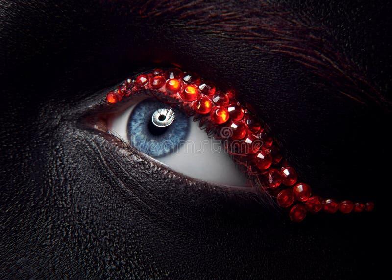 Tema criativo da composição do macro e do close-up: olho fêmea bonito com os diamantes pretos da pele e do vermelho, foto retocad fotografia de stock royalty free