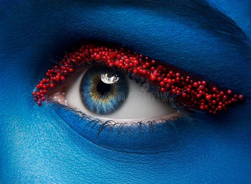 Tema criativo da composição do macro e do close-up: Olho fêmea bonito com pintura azul na cara e em bolas vermelhas pequenas do c imagens de stock royalty free
