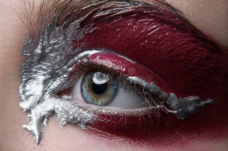 Tema criativo da composição do macro e do close-up: olho fêmea bonito com pintura de prata e vermelha, foto retocada fotos de stock royalty free