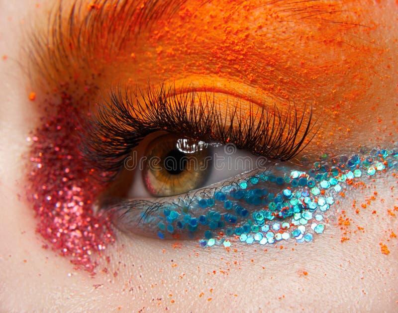 Tema criativo da composição do macro e do close-up: Olho fêmea bonito com sparkles vermelhos e do azul e o pigmento alaranjado fotografia de stock