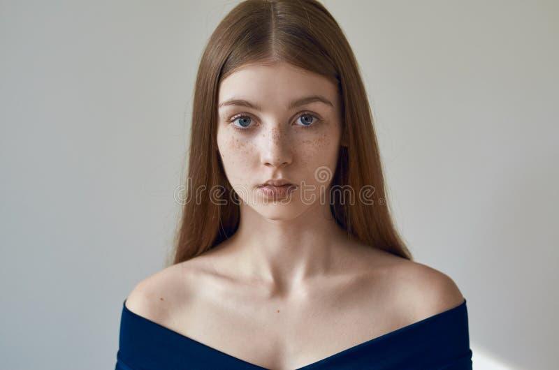Tema da beleza: retrato de uma moça bonita com as sardas em sua cara e em vestir um vestido azul em um fundo branco no studi imagens de stock royalty free
