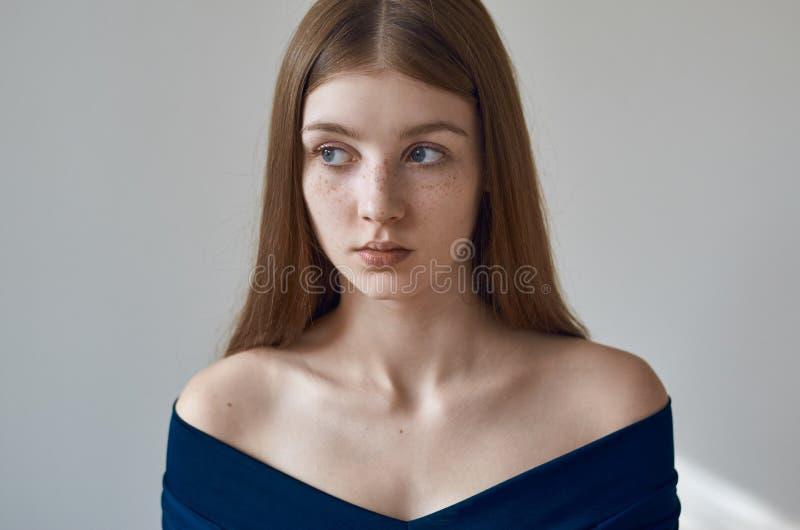 Tema da beleza: retrato de uma moça bonita com as sardas em sua cara e em vestir um vestido azul em um fundo branco no studi imagens de stock