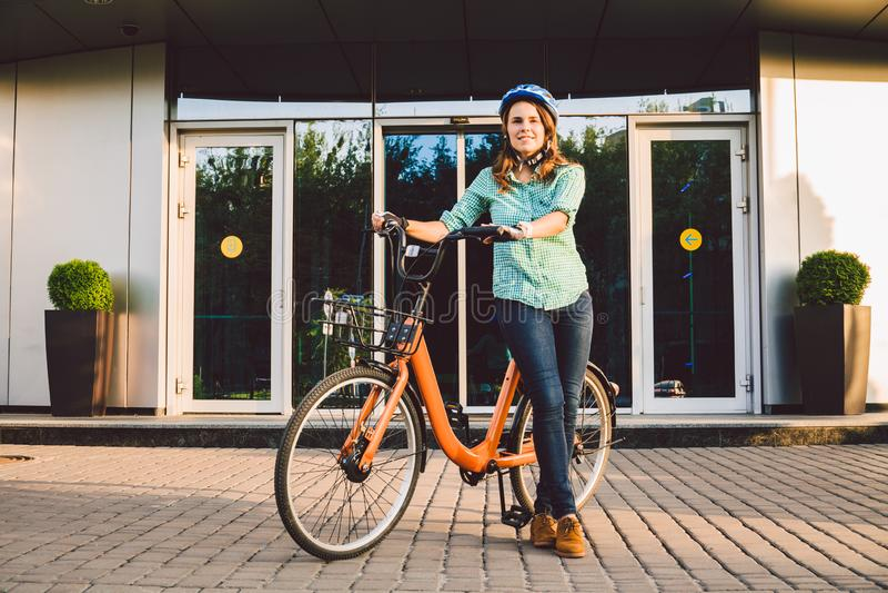Tema da lavorare alla bici Una giovane donna caucasica ? arrivato sulla bici rispettosa dell'ambiente del trasporto all'ufficio R fotografia stock