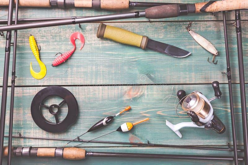 Tema da pesca O quadro das varas de pesca com equipamentos de pesca, a linha, a faca, o carretel e a pesca buoy no fundo de madei imagens de stock royalty free