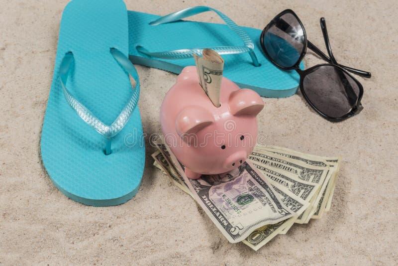 Tema das economias das férias da praia com mealheiro foto de stock