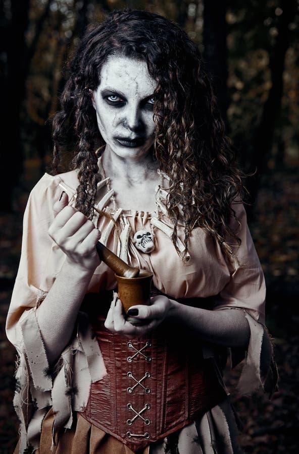 Tema de Dia das Bruxas: bruxa feia do vudu do temor com almofariz e pilão O retrato do mal encanta no vivo escuro da mulher do zo imagens de stock