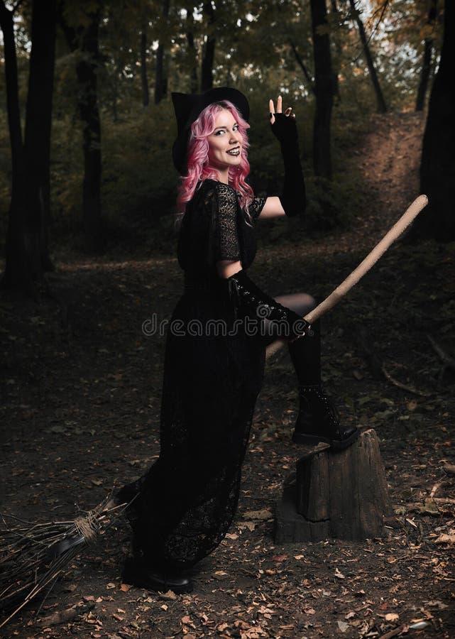 Tema de Halloween: bruja joven sonriente moderna en vestido y sombrero negros con la escoba en bosque oscuro imagenes de archivo