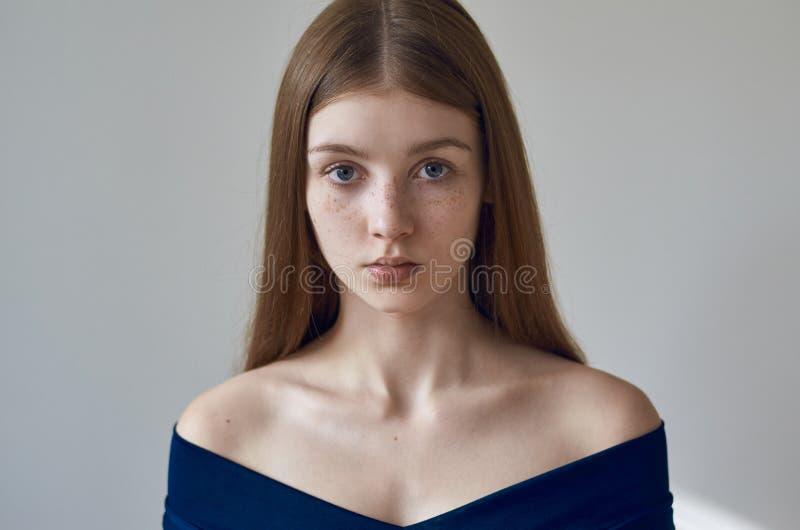 Tema de la belleza: retrato de una chica joven hermosa con las pecas en su cara y llevar un vestido azul en un fondo blanco en st imagen de archivo libre de regalías