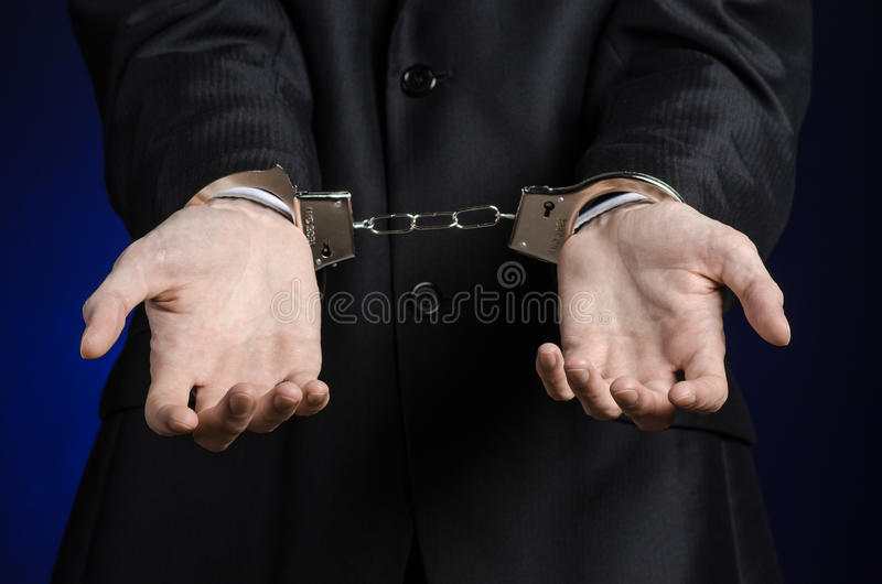 Tema de la corrupción y del soborno: hombre de negocios en un traje negro con las esposas en sus manos en un fondo azul marino en imagen de archivo libre de regalías