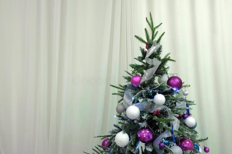 Tema de la Feliz Año Nuevo El top del árbol de navidad colgado con los juguetes contra el contexto de cortinas Copyspace foto de archivo