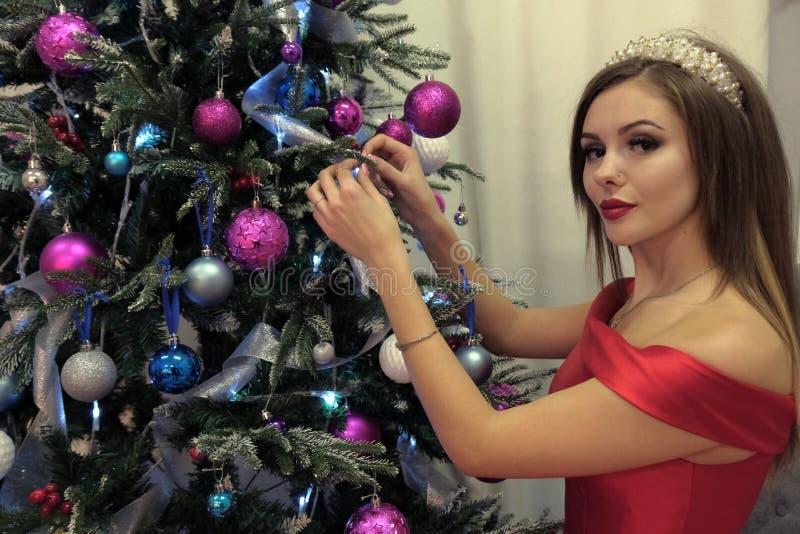Tema de la Feliz Año Nuevo y de la Navidad Una mujer hermosa cuelga para arriba los juguetes en un árbol del nuevo-año en un vest imagen de archivo