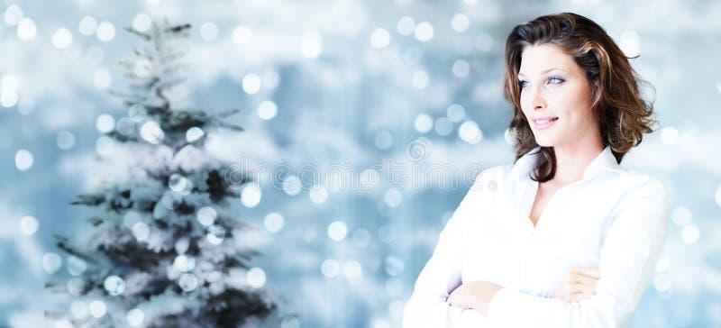 Tema de la Navidad, mujer sonriente del negocio en luces brillantes borrosas fotografía de archivo libre de regalías