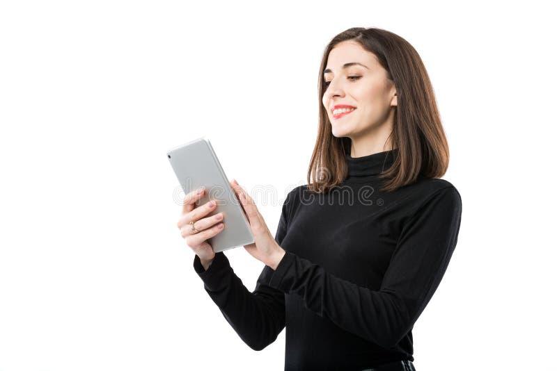 Tema de la tecnolog?a del negocio de la mujer Mujer cauc?sica joven hermosa en la camisa negra que plantea la situaci?n con las m imagen de archivo