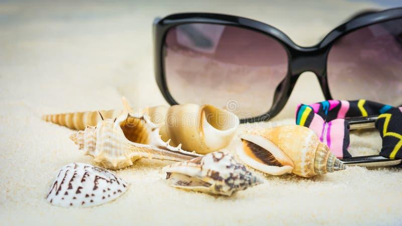 Tema de las vacaciones de verano con las cáscaras, las gafas de sol y el traje de baño del mar con el ornamento étnico en la play imágenes de archivo libres de regalías