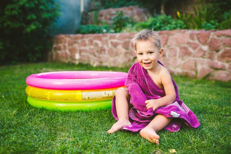 Tema de las vacaciones de verano Un pequeño muchacho caucásico de 3 años que juega en el patio trasero de una casa en la hierba c fotos de archivo libres de regalías