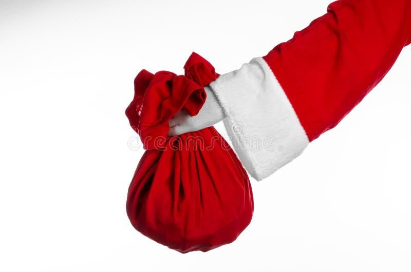 Tema de Santa Claus: Papá Noel que sostiene un saco rojo grande con los regalos en un fondo blanco imagen de archivo libre de regalías