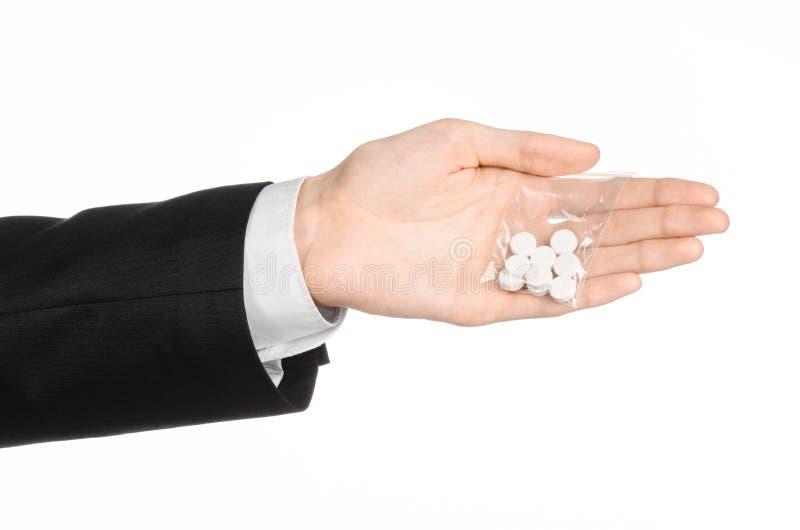 Tema del apego y del negocio: la mano en un traje negro sostiene el bolso con las píldoras blancas una droga en un fondo aislado  imagenes de archivo