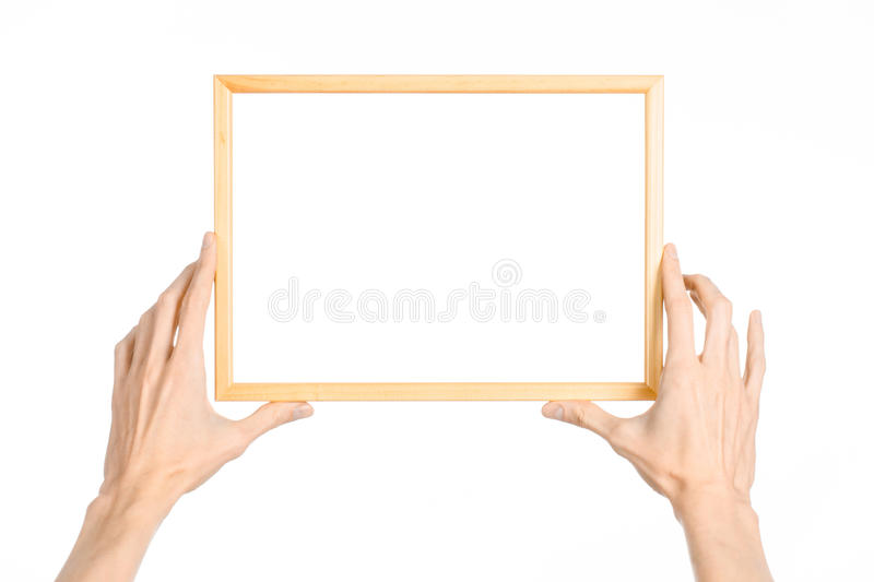 Tema del capítulo de la decoración y de la foto de la casa: mano humana que lleva a cabo un marco de madera aislado en un fondo b fotografía de archivo libre de regalías