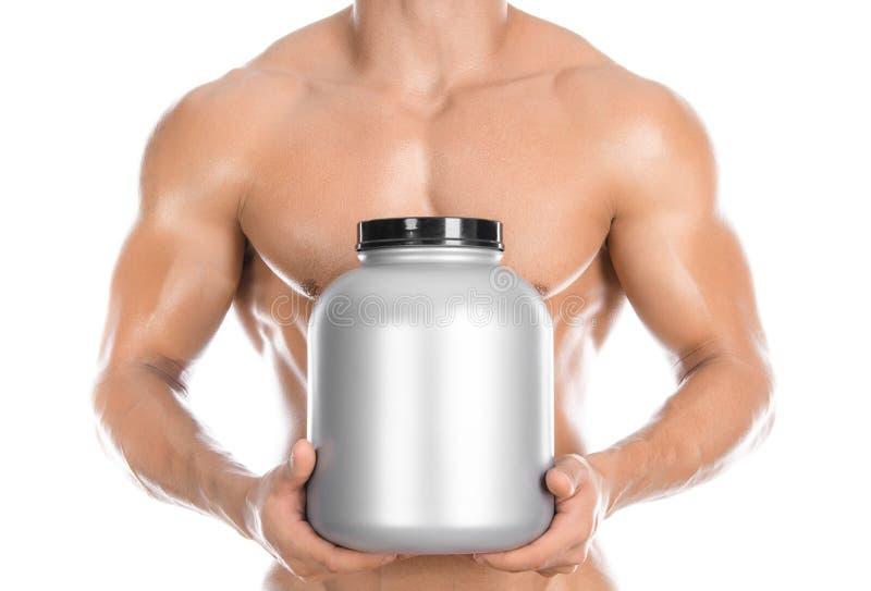 Tema del levantamiento de pesas y de los deportes: el culturista fuerte hermoso que sostenía un tarro plástico con una proteína s fotografía de archivo libre de regalías