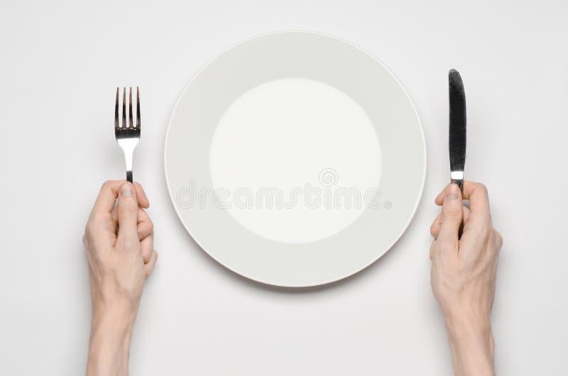 Tema del restaurante y de la comida: el gesto humano de la demostración de la mano en una placa blanca vacía en un fondo blanco e fotografía de archivo