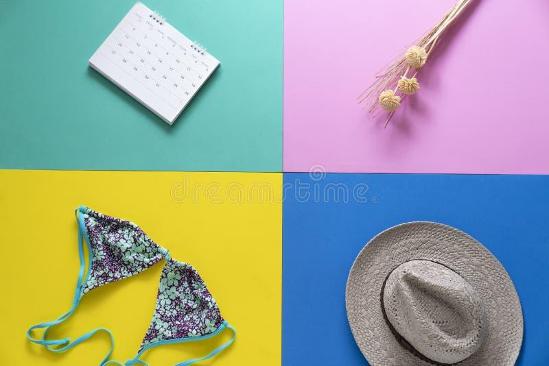 Tema del viaje, vacaciones y tiempo de verano que recuerda para prepararse para el bikini, el sombrero, la flor y el calendario foto de archivo