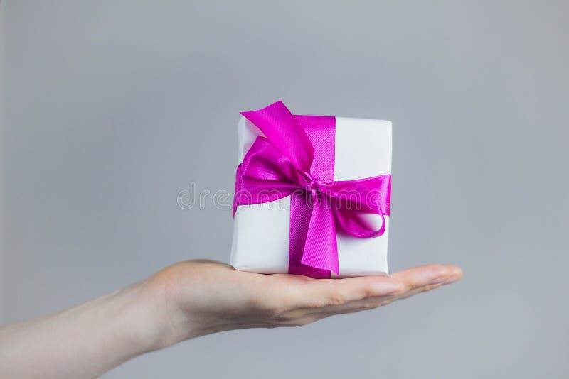 Tema delle celebrazioni e dei regali: la donna che tiene il regalo esclusivo ha imballato in scatola bianca con bello ed il regal fotografie stock