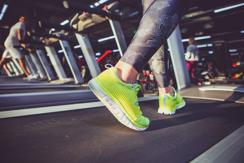 Tema dello sport e della perdita di peso Primo piano del piede di giovane forte donna in scarpe da tennis verde chiaro su un simu fotografie stock