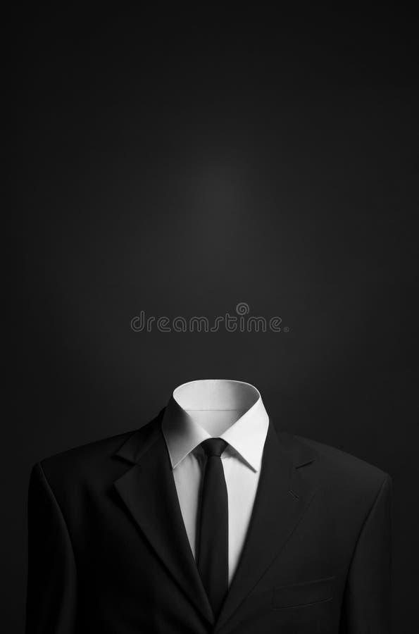 Tema di affari e di surrealismo: un uomo senza una testa in un vestito nero su un fondo scuro nello studio fotografia stock