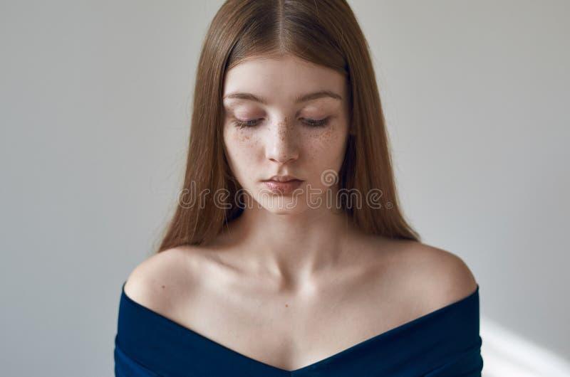 Tema di bellezza: ritratto di bella ragazza con le lentiggini sul suo fronte e sul portare un vestito blu su un fondo bianco in s fotografie stock