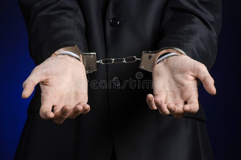 Tema di corruzione e di corruzione: uomo d'affari in un vestito nero con le manette sulle sue mani su un fondo blu scuro in studi immagine stock libera da diritti