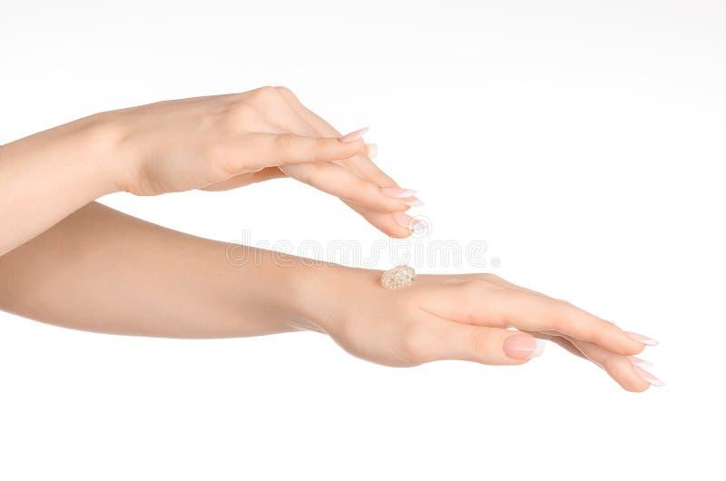 Tema di cura del corpo e di salute: la bella mano femminile con un trasparente sfrega la crema su un fondo bianco isolata fotografia stock libera da diritti