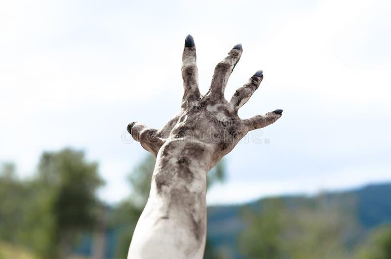 Tema di Halloween e di orrore: Le mani terribili dello zombie sporche con i chiodi neri raggiungono per il cielo, apocalisse di m immagini stock libere da diritti