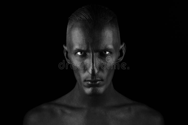Tema di Halloween e gotico: un uomo con pelle nera è isolato su un fondo nero nello studio, il body art di morte nera immagine stock