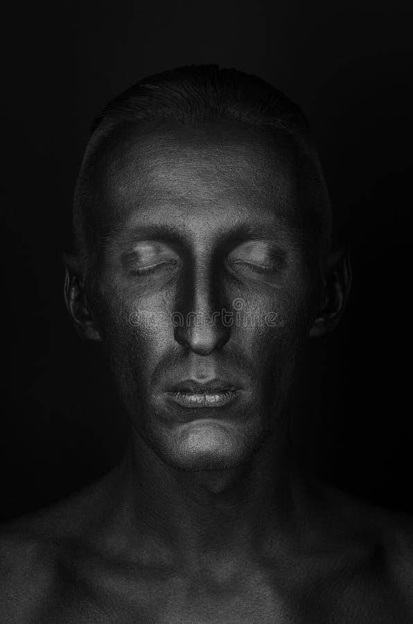 Tema di Halloween e gotico: un uomo con pelle nera è su un fondo nero nello studio, il body art di morte nera fotografia stock libera da diritti