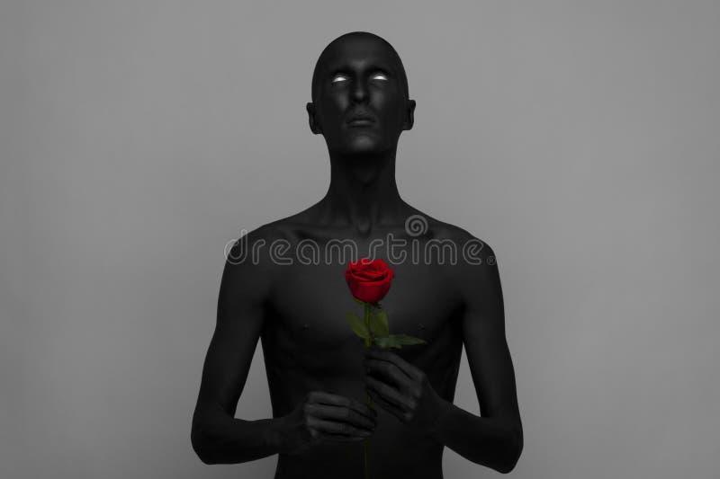 Tema di Halloween e gotico: un uomo con pelle nera che tiene una rosa rossa, morte nera isolata su un fondo grigio in studio fotografia stock