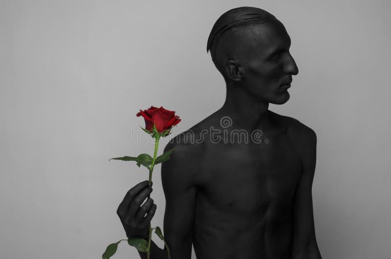 Tema di Halloween e gotico: un uomo con pelle nera che tiene una rosa rossa, morte nera isolata su un fondo grigio in studio immagini stock libere da diritti