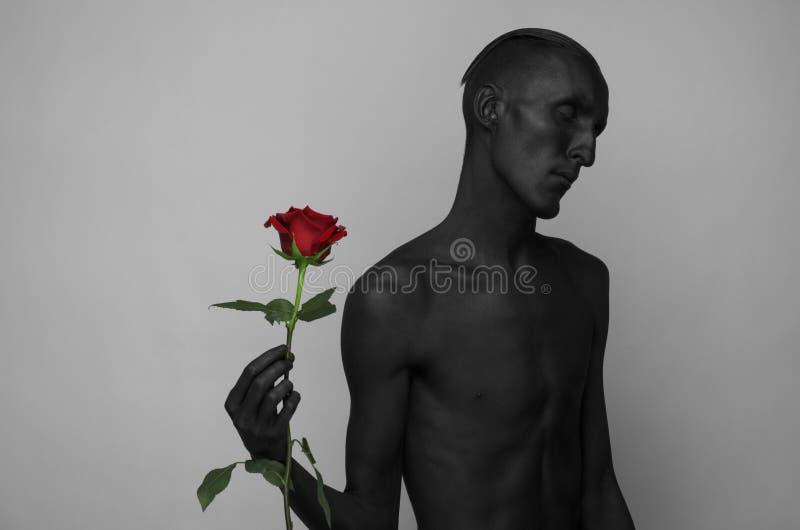 Tema di Halloween e gotico: un uomo con pelle nera che tiene una rosa rossa, morte nera su un fondo grigio in studio fotografia stock