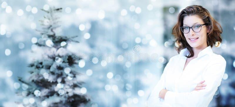 Tema di Natale, donna sorridente di affari sulle luci intense vaghe immagini stock