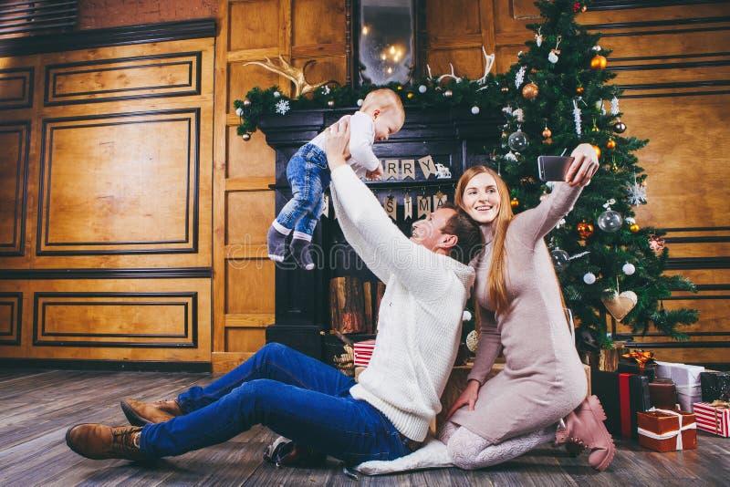 Tema di natale Il padre getta il figlio di di un anno biondo, si siede su un albero di legno davanti all'albero di Natale con i r fotografia stock