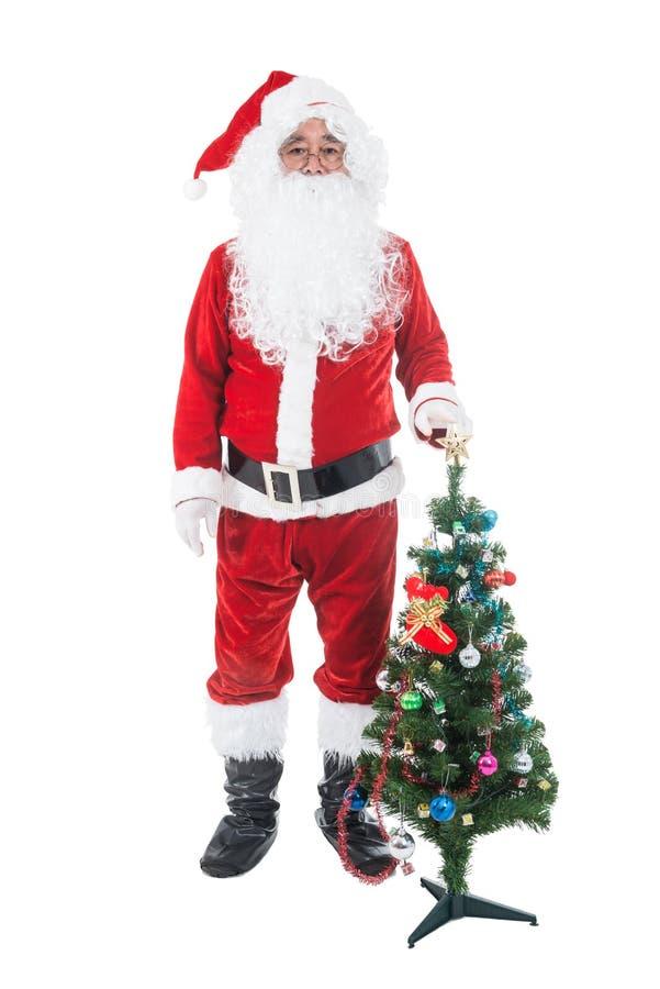 Tema di Natale - l'albero di Natale ed il suo della tenuta di Santa Claus insaccano in pieno dei regali sopra fondo bianco Santa  fotografie stock